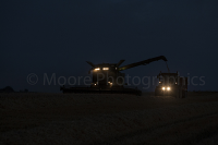 Combine Harvester at night loading a trailer