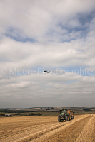 John Deere tractor with trailer being watched by an Apache Helicopter